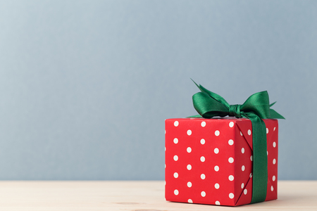 Christmas present box wrapped in red paper with polka dots and decorated with green ribbon.