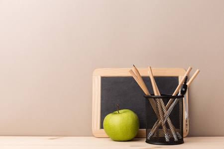 Composition of green fresh apple with pencils in organizer and small blackboard.  Stock Photo