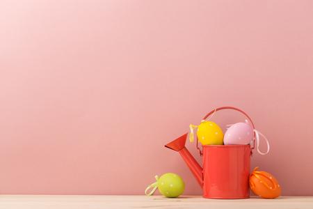 Beautiful arrangement of orange watering pot with decorative Easter eggs.