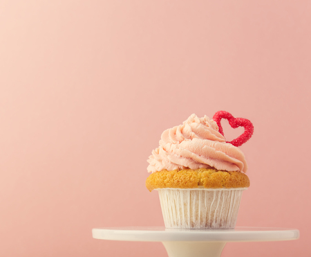 Closeup of small muffin with pin frosting decorated with small heart and composed on cake stand.