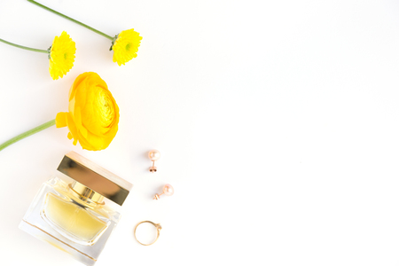 Top view of minimalist composition with yellow spring flowers and female perfume with jewelry.