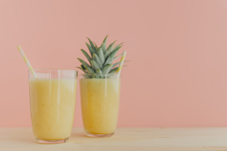 Two glasses filled with freshly made pineapple smoothie and served with colorful straws.
