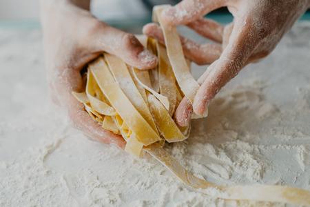 Close-up van het proces om zelfgemaakte deegwaren te koken. Chef-kok maakt verse Italiaanse traditionele pasta