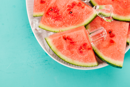 Closeup of fresh cut watermelon slices on ice cubes on plate on blue background. Summer concept