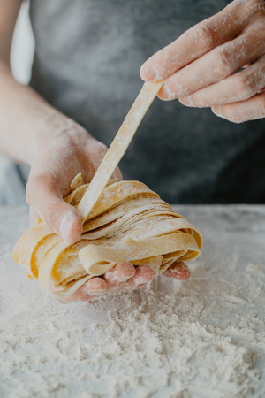 Closeup of process of making cooking homemade pasta. Chef make fresh italian traditional pasta