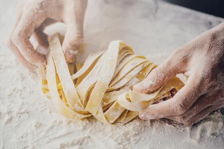 Nahaufnahme des Prozesses der Herstellung von hausgemachten Nudeln. Chefkoch machen frische italienische traditionelle Pasta
