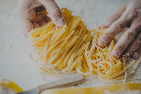 Close-up van het proces om zelfgemaakte deegwaren te koken. Chef-kok maakt verse Italiaanse traditionele pasta Stockfoto