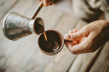 Young man pouring tasty hot coffee from iron turk to cup. Closeup
