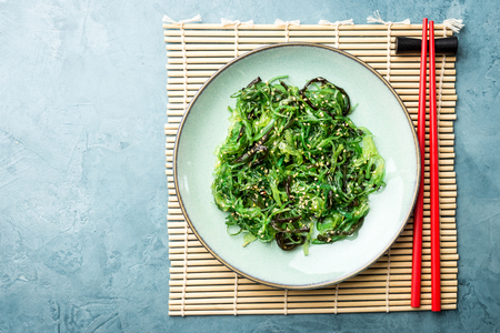 Tasty appetizing seaweed salad on plate on table. Top View with Copy Space Reklamní fotografie