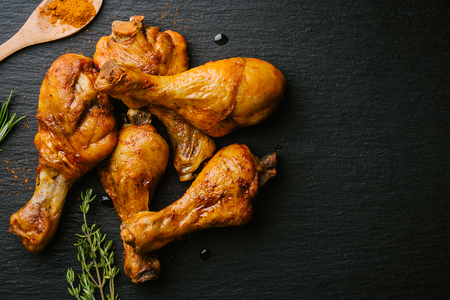 Tasty appetizing roasted bbq chicken legs with spices on black slate background. View from above with copy space.