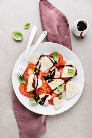Valentine's Day salad. Italian classic caprese salad with heart formed mozzarella, basil, balsamico and tomatoes served on plate. Above view. Copy space. Standard-Bild - 114371092