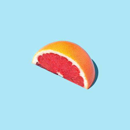Beautiful food fashion concept with half slice of grapefruit on blue background. Square.