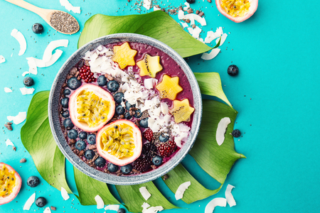 Tasty appetizing smoothie acai bowl made from blackberries and wild berries, decorated with cut passion fruit, coconut flakes, and cacao nibs. Served in bowl. Healthy life clean eating concept. Top View. Horizontal. Standard-Bild - 114371097