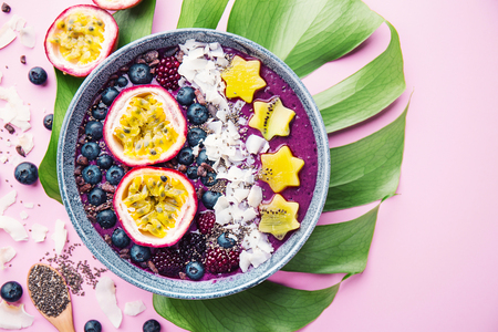 Tasty appetizing smoothie acai bowl made from blackberries and wild berries, decorated with cut passion fruit, coconut flakes, and cacao nibs. Served in bowl. Healthy life clean eating concept. Top View. Horizontal. Standard-Bild - 114371100