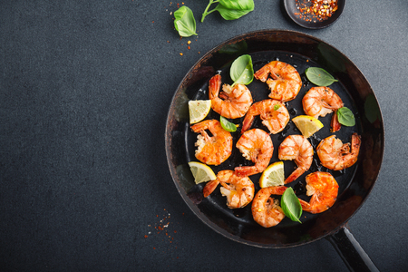 Tasty appetizing fried grilled shrimps with spices on black pan. View from above with copy space.
