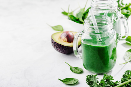 Fresh made healthy green smoothie served in jars on bright table. Fruits and vegetables ingredients around. Closeup with Copy space. Horizontal. Standard-Bild - 114631441