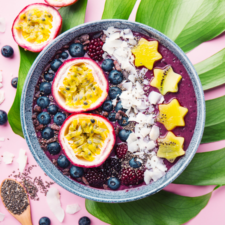 Tasty appetizing smoothie acai bowl made from blackberries and wild berries, decorated with cut passion fruit, coconut flakes, and cacao nibs. Served in bowl. Healthy life clean eating concept. Square 스톡 콘텐츠