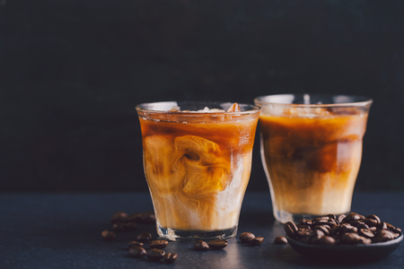 Tasty fresh cold iced coffee with milk in glasses on table. Horizontal with copy space. Standard-Bild - 114631454