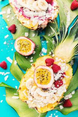 Tasty appetizing smoothie bowls served in half pineapple decorated with cut passion fruit, coconut flakes, and chia seeds.Healthy life clean eating concept. Top View.  스톡 콘텐츠