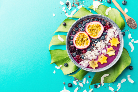 Tasty appetizing smoothie acai bowl made from blackberries and wild berries, decorated with cut passion fruit, coconut flakes, and cacao nibs. Served in bowl. Healthy life clean eating concept. Top View. Horizontal. Standard-Bild - 114631575