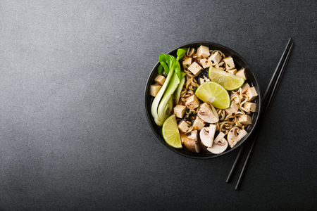 Tasty asian vegetarian or vegan soup served in black bowl on dark table. View from above. Horizontal. Standard-Bild - 114631578