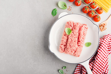 Fresh raw minced meat with spices on pan ready to be cooked. Grey background, horizontal with copy space. Closeup. Italian kitchen, bolognese sauce cooking. 스톡 콘텐츠 - 114631585