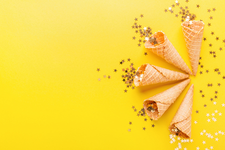 Ice cream cones with golden shining stars on yellow background. Party Happy Birthday Anniversary Background. Standard-Bild - 114631587