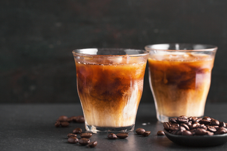 Tasty fresh cold iced coffee with milk in glasses on table. Horizontal with copy space. Standard-Bild - 114631588