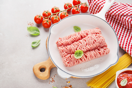 Fresh raw minced meat with spices on pan ready to be cooked. Grey background, horizontal with copy space. Closeup. Italian kitchen, bolognese sauce cooking.