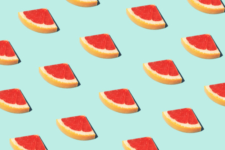 Beautiful food pattern, food fashion concept with half slices of grapefruit on blue background.