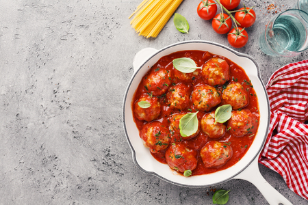 Homemade meatballs with tomato sauce and spices served in white pan on grey background. Closeup with copy space.