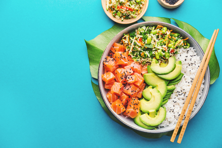 Tasty appetizing poke bowl served with salmon, avocado, rice, salad with edamame. Blue background. View from above. Horizontal. 스톡 콘텐츠