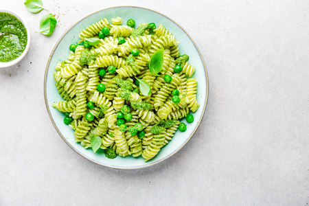 Tasty appetizing italian pasta al bronzo with pesto sauce, green pea, basil and cheese served on plate. View from above with copy space.