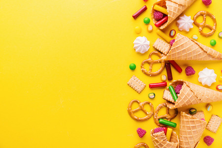 Tasty funny Sweets with Ice Cream Cones on Yellow Background. Party Happy Birthday background. Party Concept