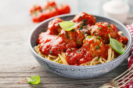 Tasty appetizing pasta with meatballs and tomato sauce in blue bowl on old wooden background. Closeup with copy space. 스톡 콘텐츠