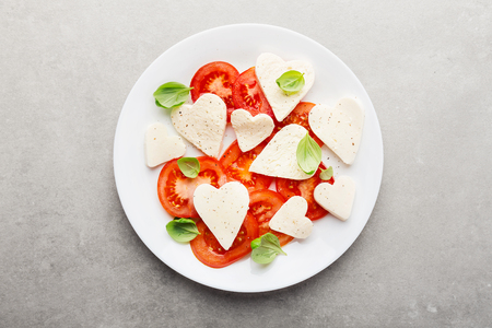 Valentines Day salad. Italian classic caprese salad with heart formed mozzarella, basil and tomatoes served on plate. Above view. Copy space.