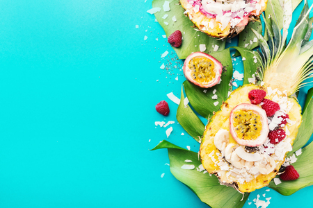 Tasty appetizing smoothie bowls served in half pineapple decorated with cut passion fruit, coconut flakes, and chia seeds.Healthy life clean eating concept. Horizontal 스톡 콘텐츠