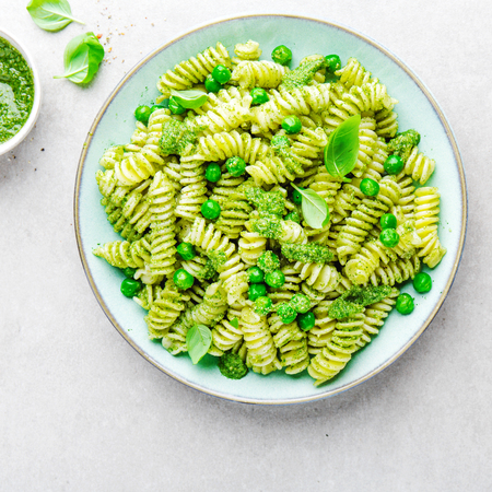 Tasty appetizing italian pasta al bronzo with pesto sauce, green pea, basil and cheese served on plate. View from above with copy space. Square. 스톡 콘텐츠