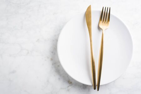 Beautiful gold cutlery - fork, knife on marble background. Horizontal.