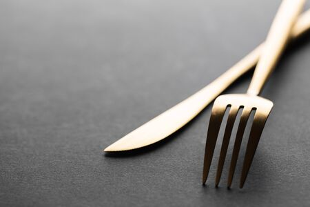 Beautiful gold cutlery - fork, knife on black background. Horizontal.