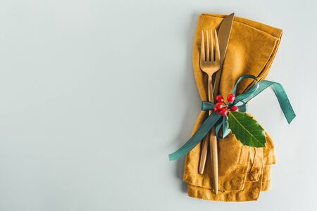 Christmas cutlery with napkin served on table.