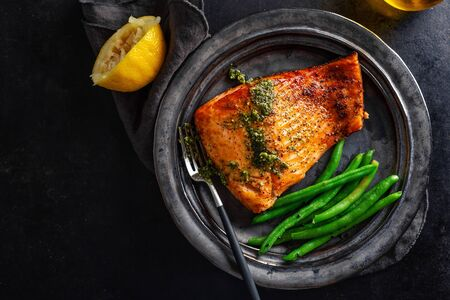 Closeup of baked salmon fish with green beans on plate on dark background