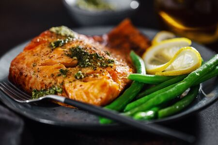 Closeup of baked salmon fish with green beans on plate.