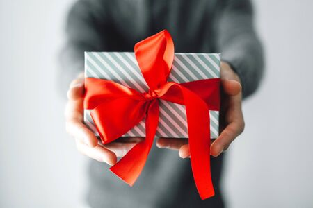 Young man holding gift with red ribbon. Closeup