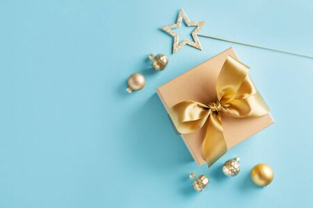 Cute gift box with golden ribbon bow on blue background with golden baubles. Flat Lay.
