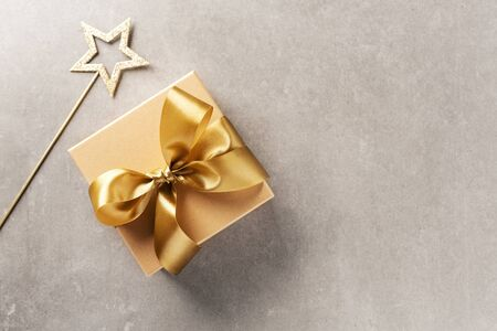 Cute gift box with golden ribbon bow on grey background. Flat Lay.