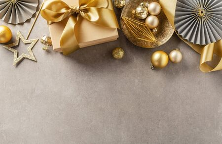 Cute gift box with golden ribbon bow on grey background. Flat Lay. Christmas background. 스톡 콘텐츠