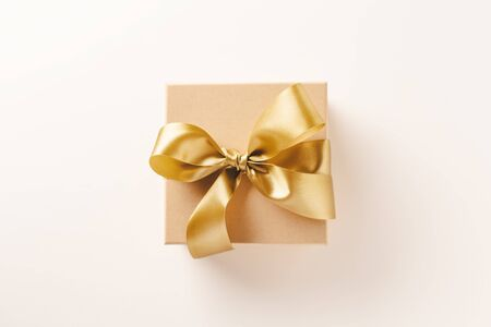 Cute gift box with golden ribbon bow on bright background. Flat Lay. 스톡 콘텐츠