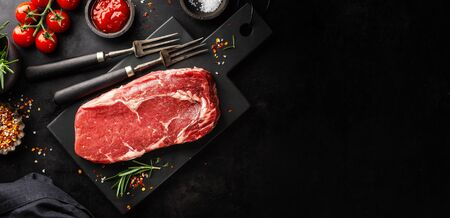 Raw beef meat on board with ingredients ready for cooking. Dark background. Cooking concept. Banner. Horizontal 스톡 콘텐츠