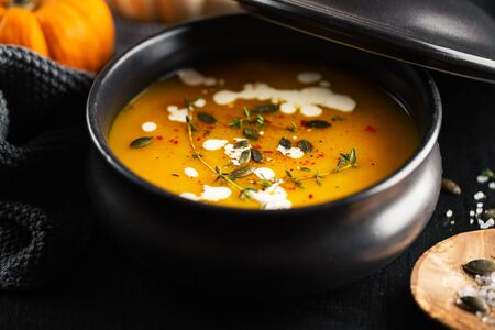 Tasty appetizing pumpkin creamy soup decorated with cream served in bowl on dark background. Closeup. 스톡 콘텐츠